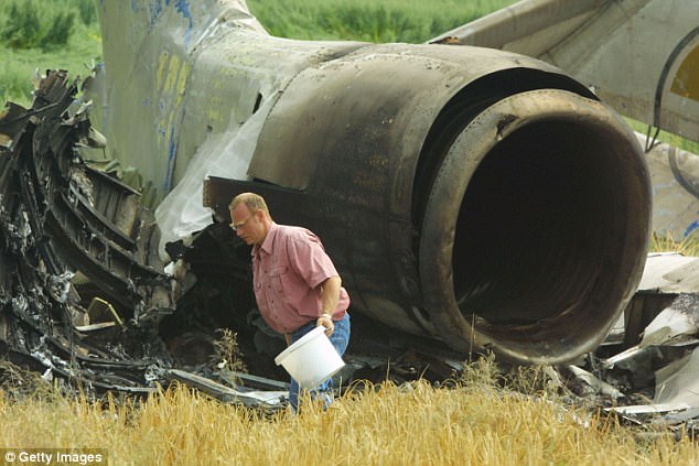 German water inspector takes soil samples by the tail wreckage of a Bashkirian Airlines plane