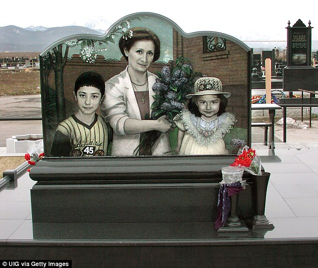 The tombstone with portraits of family members of construction engineer Vitaly Kaloyev. His wife Svetlana is holding flowers in the centre flanked by her daughter Diana (right) and son Konstantin (left)
