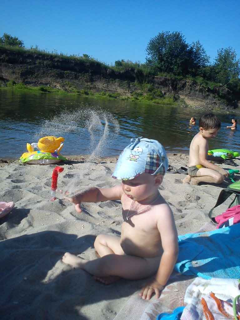 Малыш играет в песок на реке